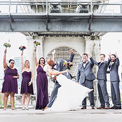Groom dipping bride under bridge with bridal party