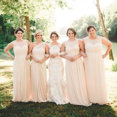 Bride linking arms with bridesmaids in neutral dresses