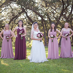 Bride posing surrounded by bridesmaids in purple