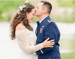 Military groom kissing bride on forehead