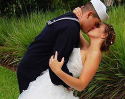 Navy groom kissing bride in romantic embrace