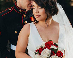 Close up of military groom and bride with red and white bouquet