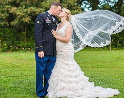 Military groom and bride kissing outdoors with veil flowing