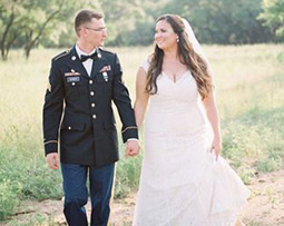 Military groom and bride holding hands walking outdoors