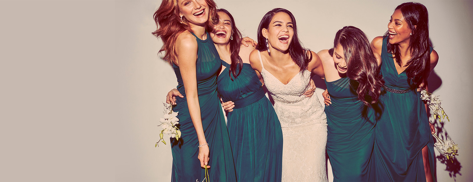 Bride and Bridesmaids with their arms around each other laughing