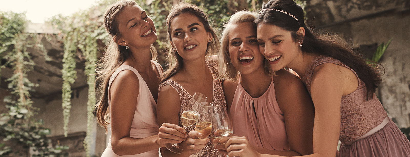Bridesmaids in pink toasting champagne on a terrace