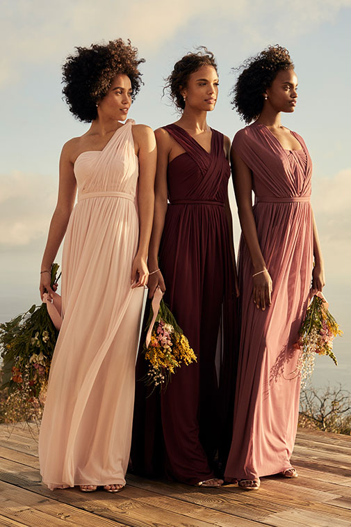 Three bridesmaids standing on a cliff side in different shades of pink holding wildflower bouquets