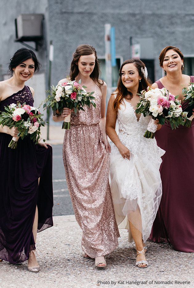 Bride and bridesmaids crossing an intersection holding their bouquets