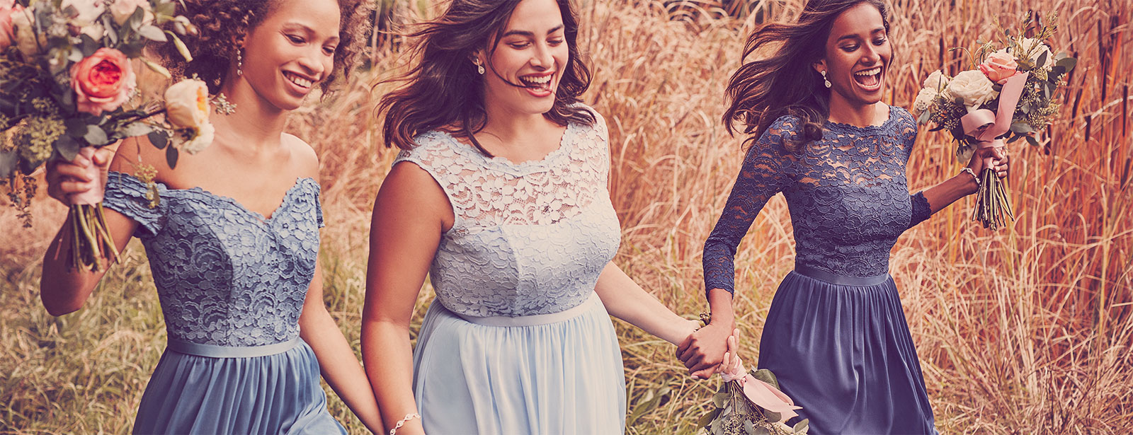 Bridesmaids running through a field holding hands and their bouquets