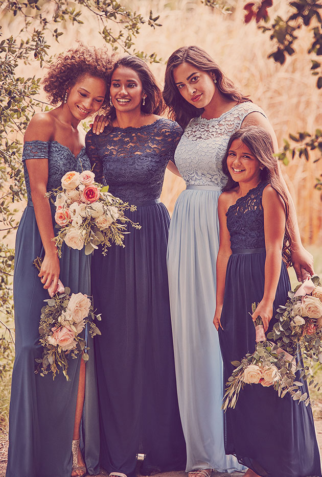 Bridesmaids and a junior bridesmaids posing in their blue lace dresses
