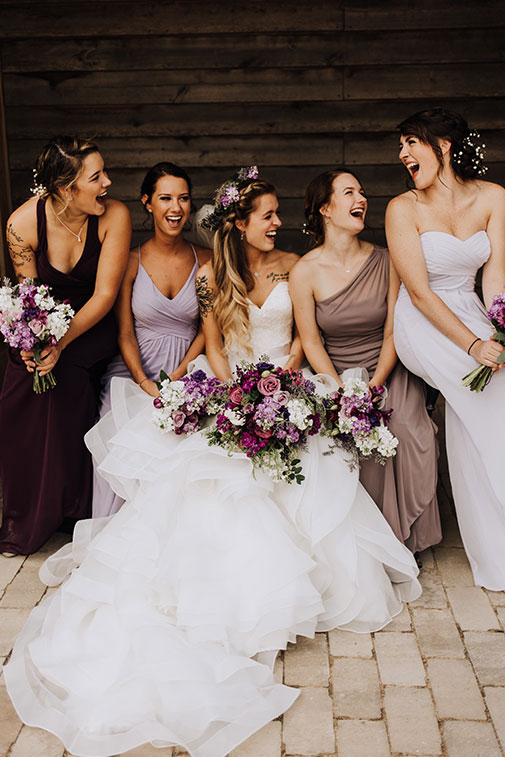 Bride sitting surrounded by her maids holding purple bouquets