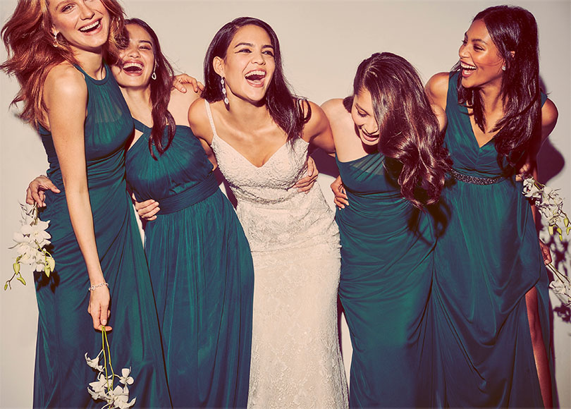 bcc7de9e719 ... Bride and Bridesmaids with their arms around each other laughing