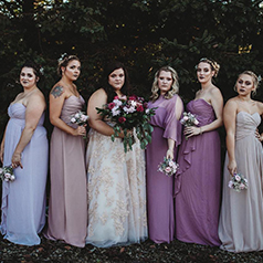 Multicolor bridal party wearing shades of light purple