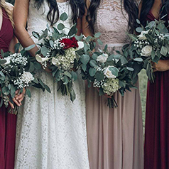 Close up of bridal party in various shade of wine and purple and their bouquets