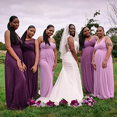 Bride with purple bouquets on her train with bridesmaids in purple dresses surrounding her