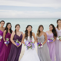 Bridesmaids in various shades of purple with bride on the beach