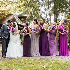 Bridesmaids in different shades of wine and purple posing with bride and groom