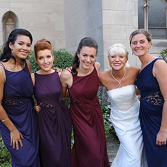 Bride posing with bridesmaids in jewel tone purple and blue dresses