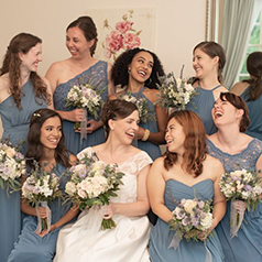 Bride surrounded by bridesmaids holding bouquets
