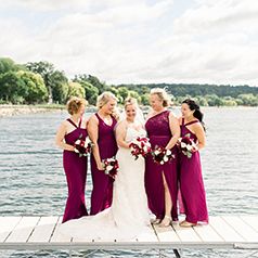 Bride and bridesmaids in fuchsia dresses posing on a dock by the water