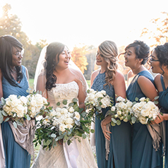 Bride with bridesmaids in blue dresses holding white bouquets