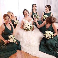 Bride holding white peony bouquet surrounded by bridesmaids in green dresses on the floor