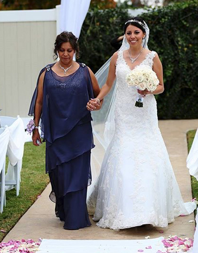 Mother of the bride wearing a navy dress walking bride down the aisle