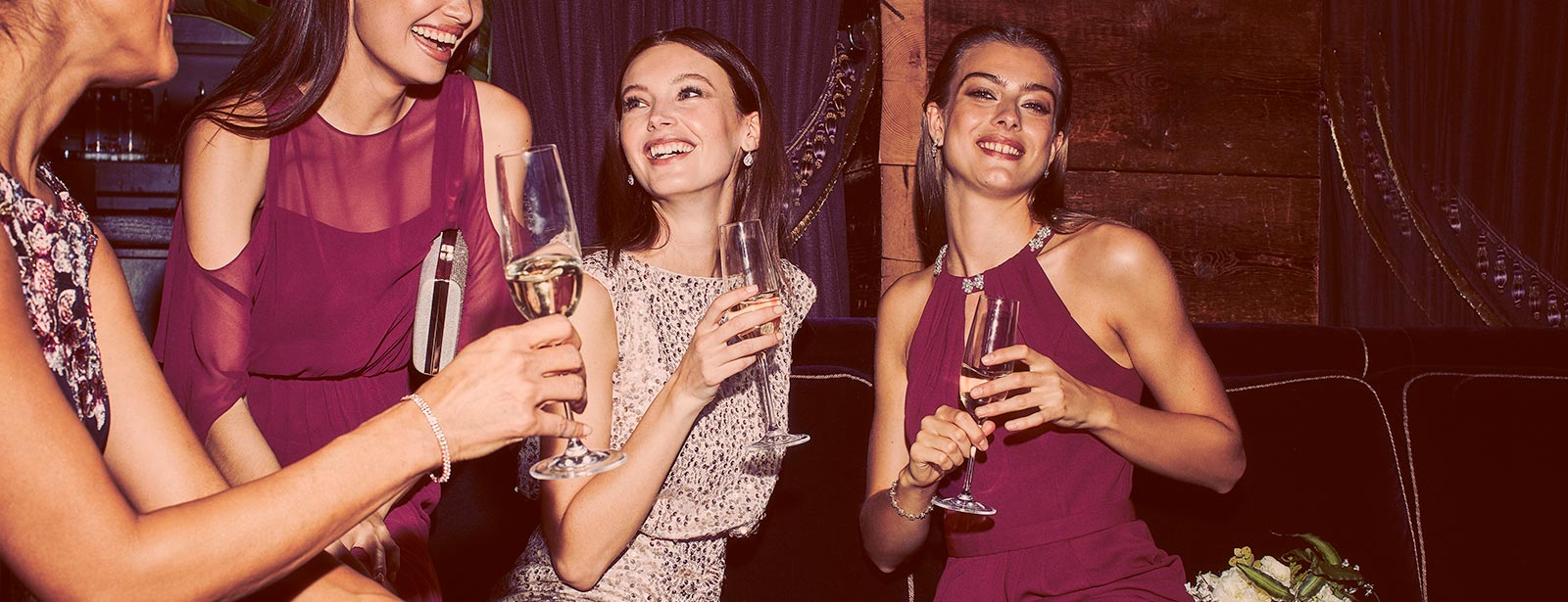 Four bridesmaids in mismatched dresses holding champagne glasses