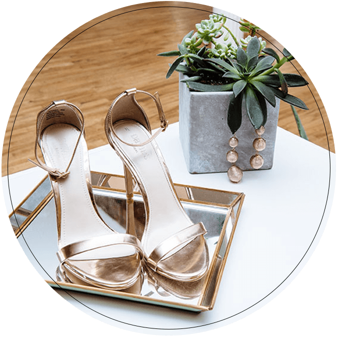 Tray with rose gold strappy heels and rose gold earrings on a plant
