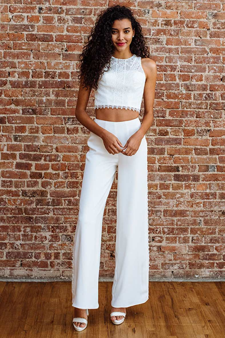 Two-piece white wide leg pants and lace crop top with white strappy heels