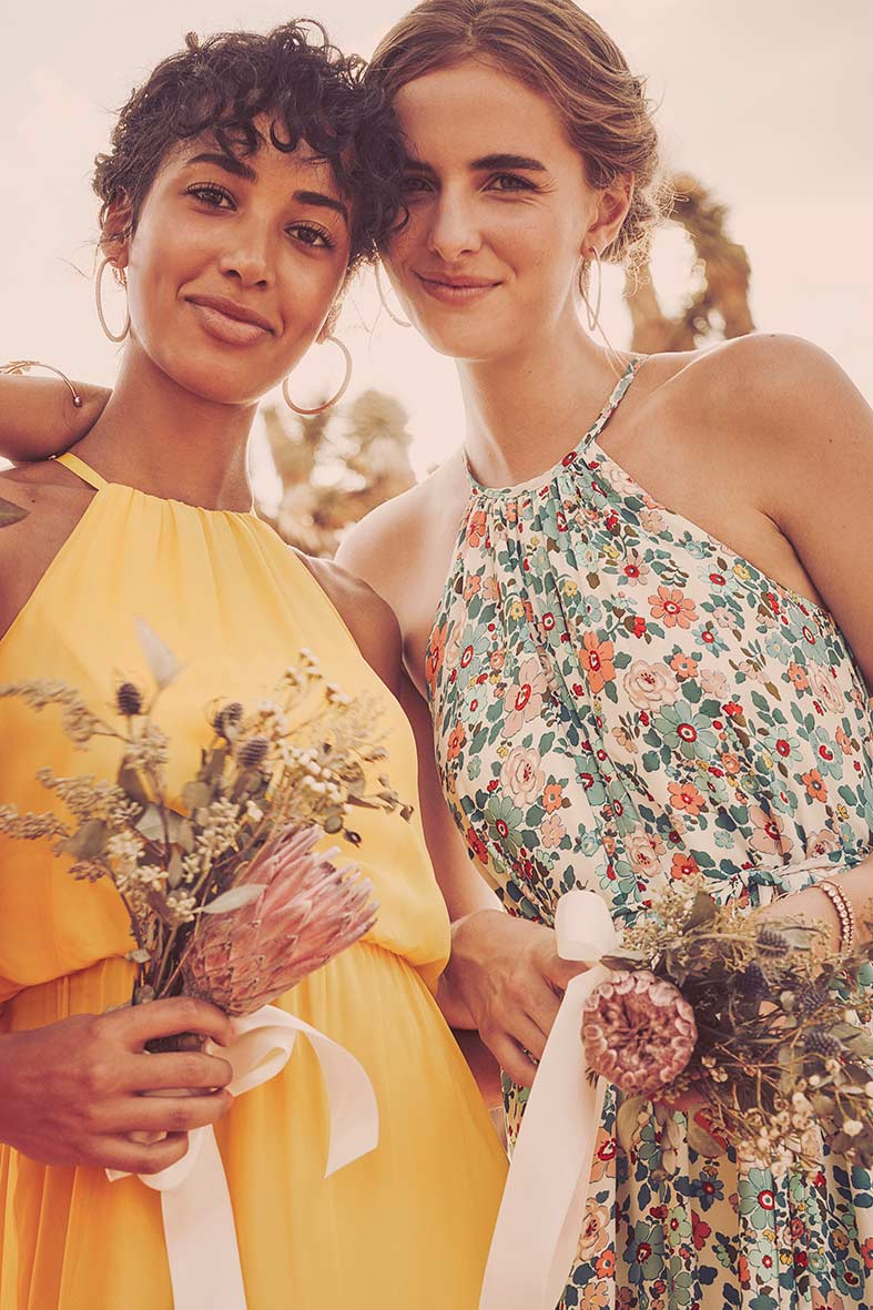 Bridesmaids holding flowers, bright yellow dress and floral print dress