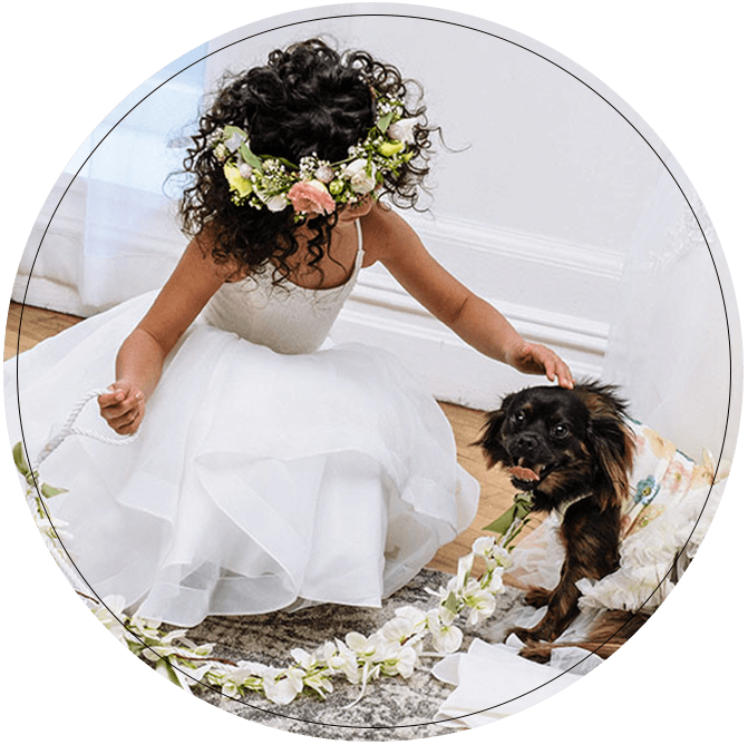 Flower girl wearing flower crown petting a dog wearing a dog tux