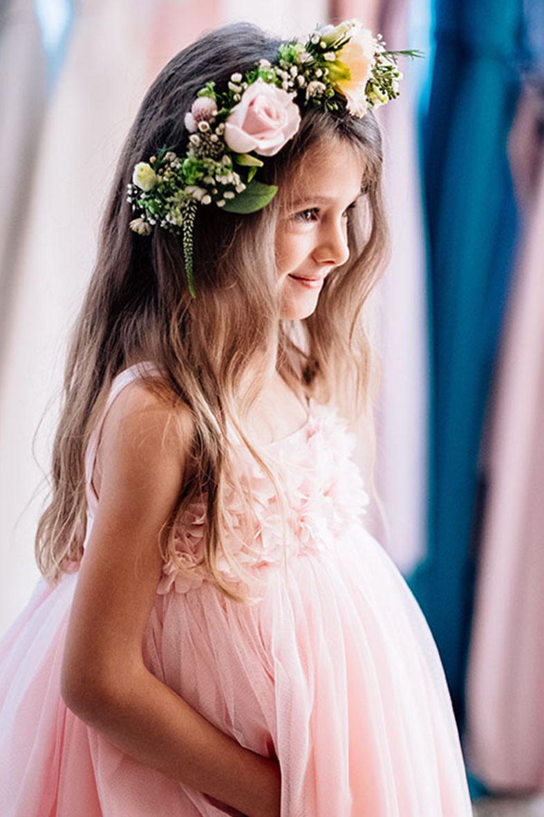 Flower girl wearing a colorful flower crown and pink dress with flower bodice and full skirt