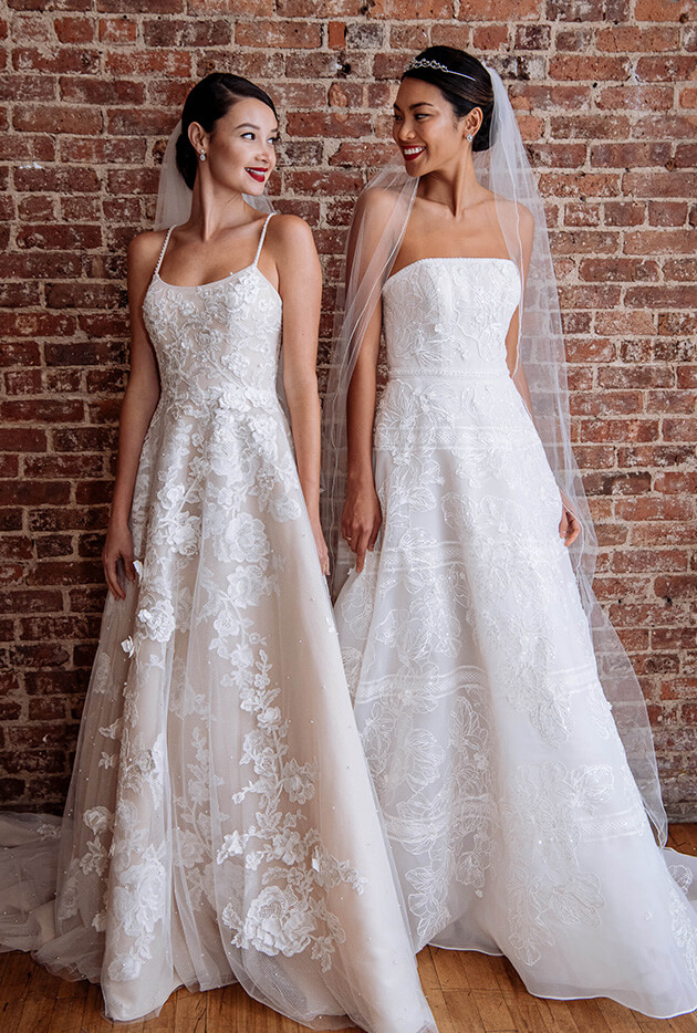 Two brides wearing long wedding dresses with veils.