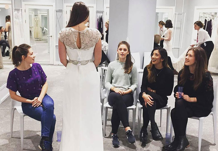 Bride talking to her friends in front of fitting rooms at bridal shop