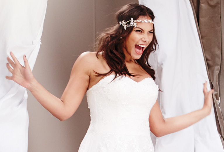 Surprised, happy bride coming out of dressing room