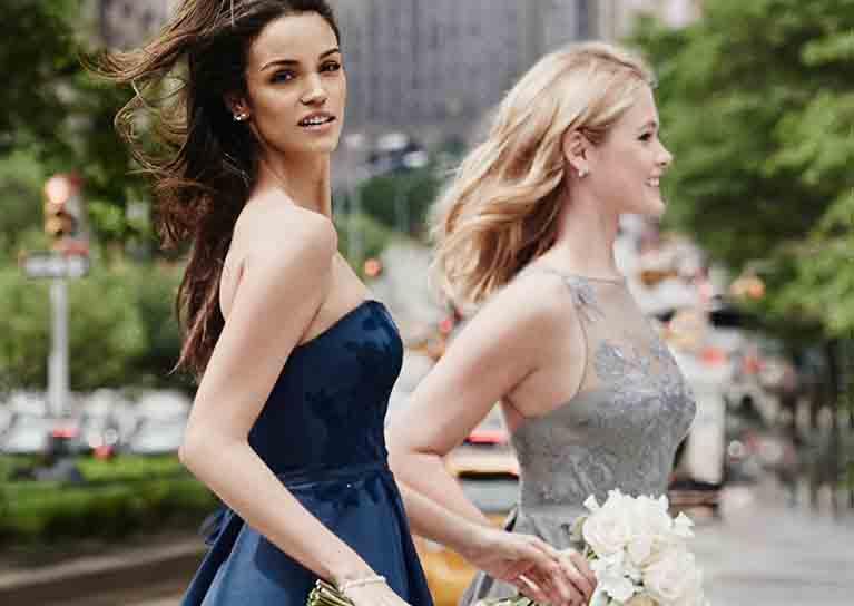 Two bridesmaids crossing a city street in navy dress and silver embroidered dress