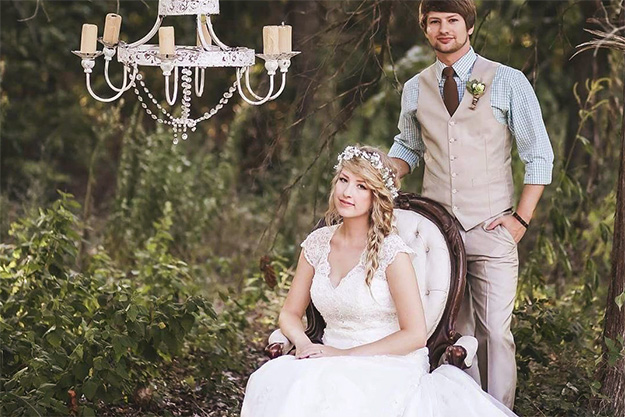 Bride seated outdoors under chandelier with groom standing behind her