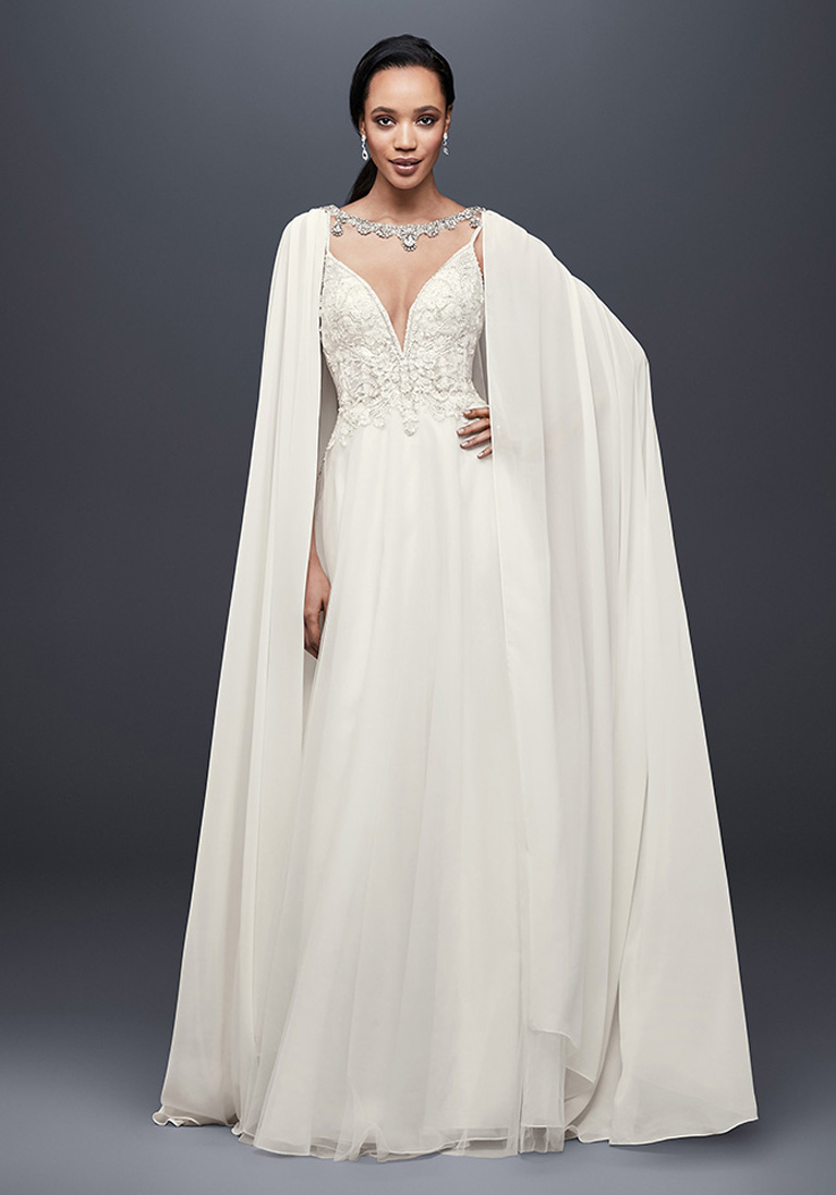 Bride wearing draping cape with wedding gown.