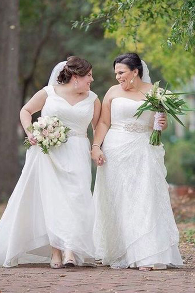 Two real brides wearing plus size wedding dresses walking outdoors
