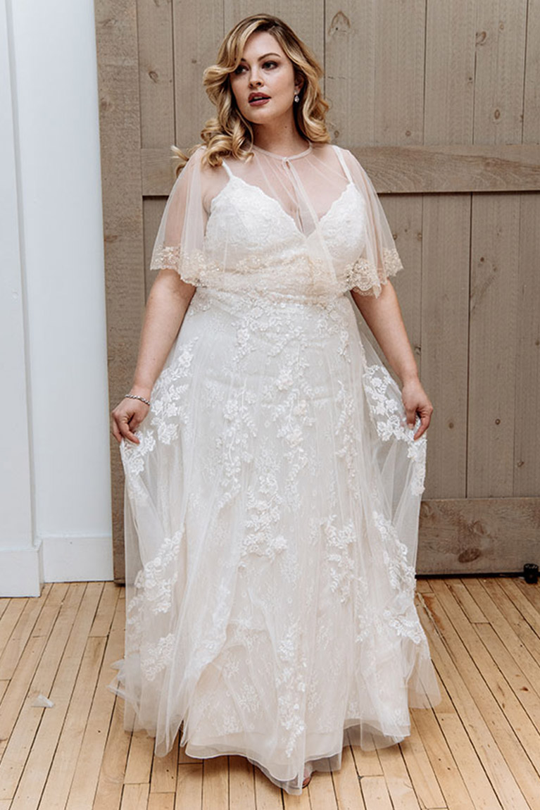 Plus size bride wearing lace wedding dress and bridal topper