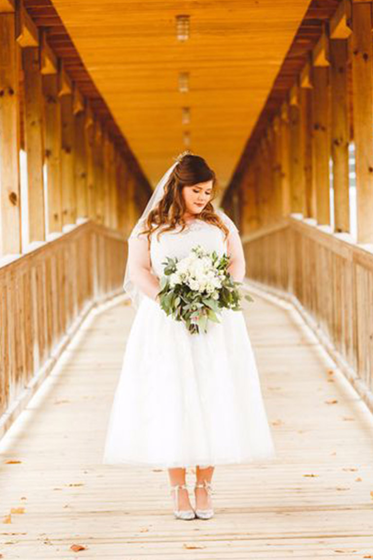 Bride on a rustic wooden bridge wearing plus size tea-length wedding dress