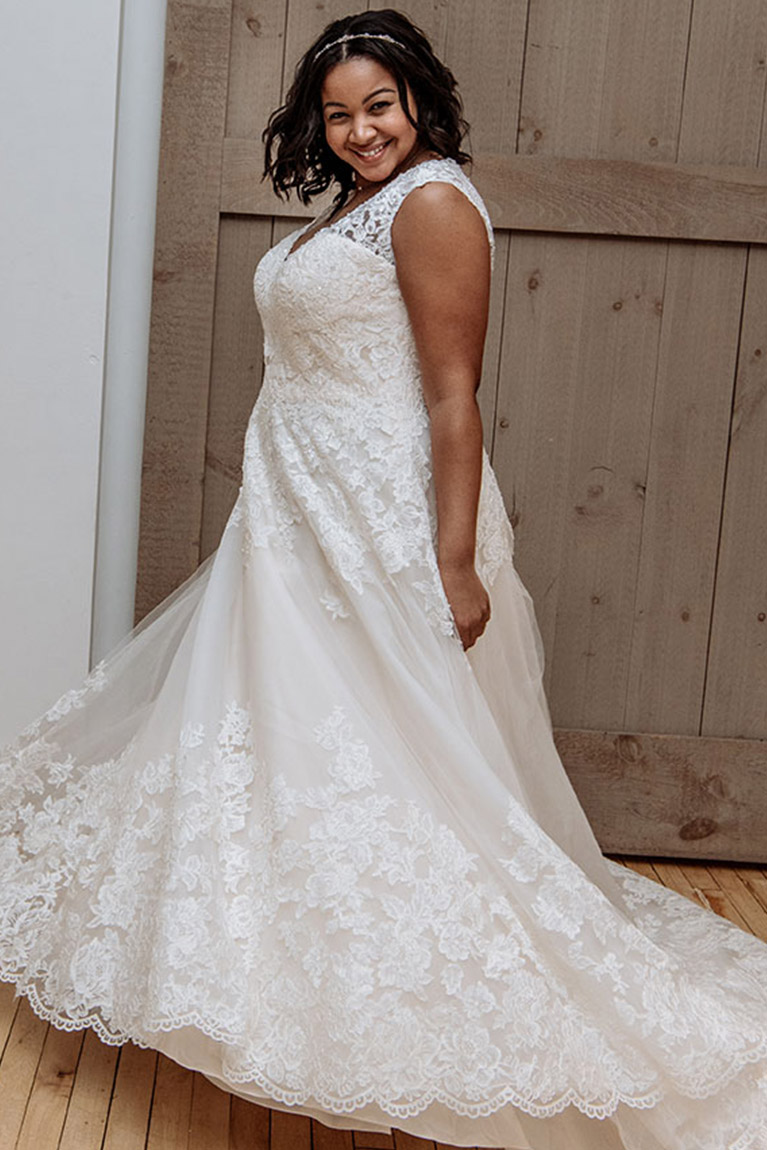 8d9487d1fc1 Bride taking a spin in a plus size lace wedding gown in front of barn door