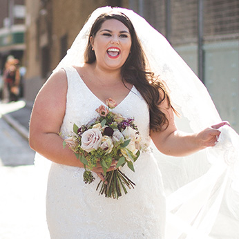 Real plus size bride wearing cathedral veil and holding bouquet