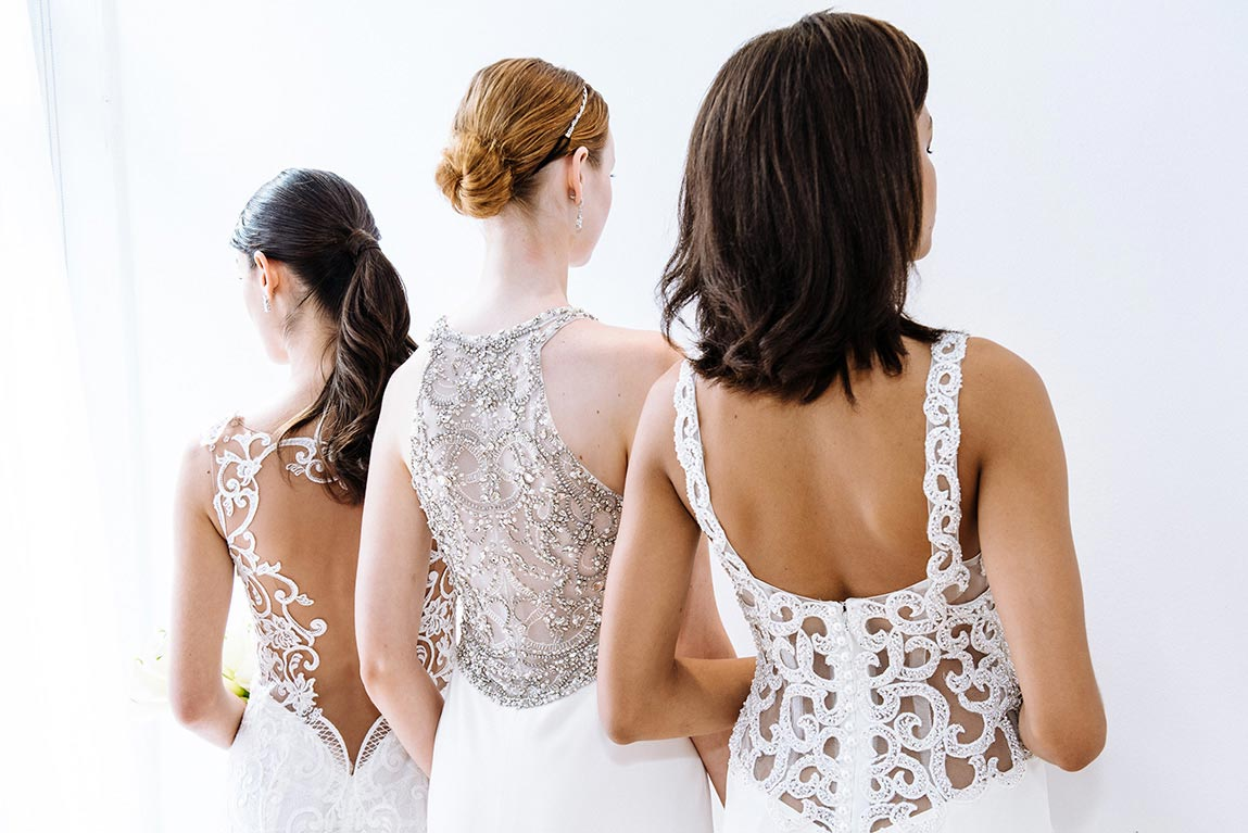 Three brides modeling back of dresses