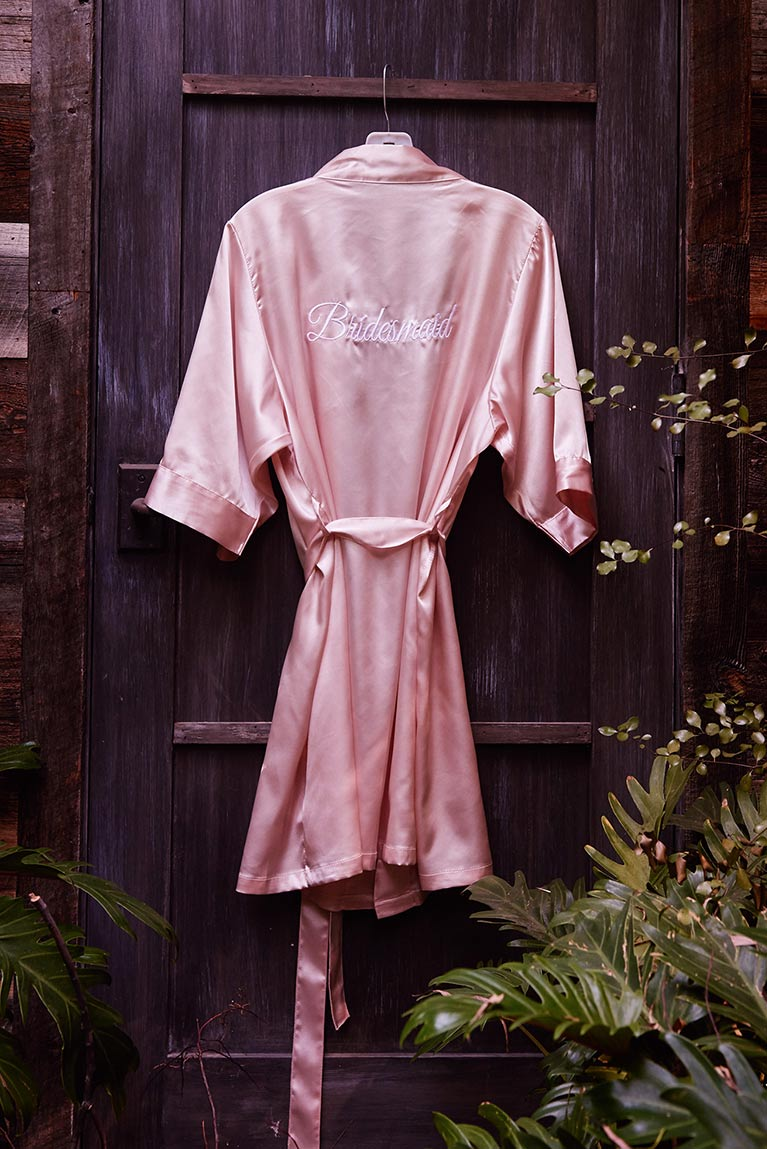 Hanging pink robe with Bridesmaid stitched on the back