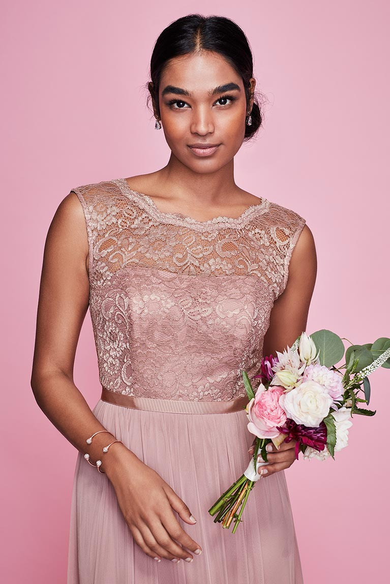 Woman In A Pink Bridesmaid Dress Holding Flowers