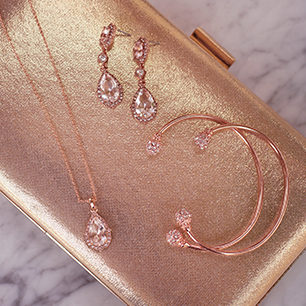 Gold purse with rose gold earrings, necklace, and bracelets