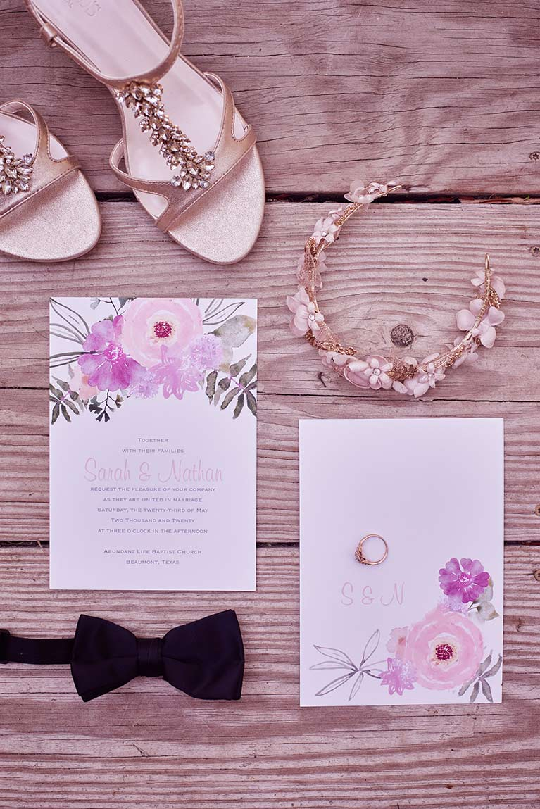 Pink wedding invitations with a bowtie, pink shoes, and flower crown
