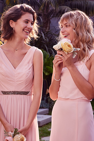 Two bridesmaids in petal pink bridesmaids dresses holding flowers